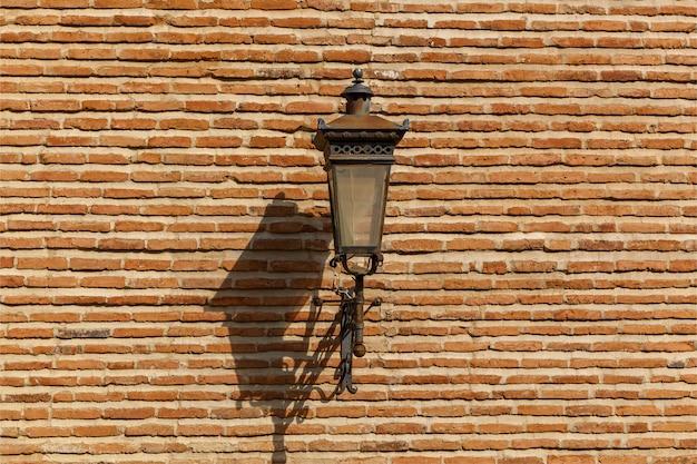Latarnia uliczna na ścianie ogrodzenia z kamienia