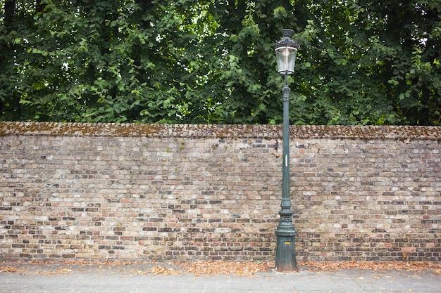 Latarnia uliczna po prawej stronie na ceglanej ścianie