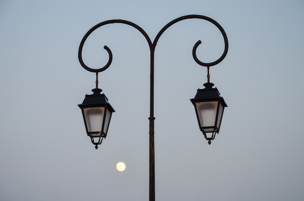 Latarnia uliczna wieczorem na tle księżyca na wybrzeżu grecji (heraklion)