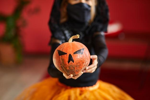 Latarnia z dyni, dynia halloween w ochronie medycznej czarna maska w rękach dziewczyny podczas uroczystości halloween w domu covid19 pandemia koronawirusa, kopia przestrzeń