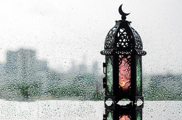 Latarnia z symbolem księżyca na górze umieszczona na oknie z kroplą deszczu na islamski nowy rok