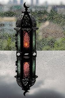 Latarnia z symbolem księżyca na górze umieszczona na oknie z kroplą deszczu
