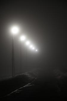 Latarnie wzdłuż nocnej drogi we mgle