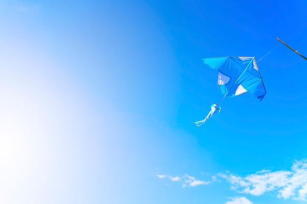 Latawiec latający na błękitnym niebie z bezpłatną kopii przestrzenią. koncepcja podróży i życia wolności.