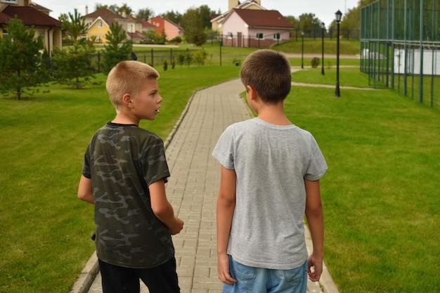 Latem dwaj przyjaciele chłopcy idą ścieżką. przyjaźń chłopca dla dzieci.