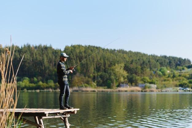 Latem mężczyzna łapie rybę na spinning