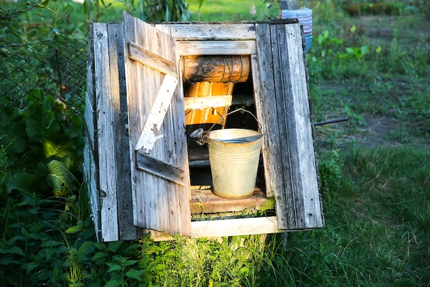 Latem na zewnątrz drewniana studnia. wiadro z wodą. archiwalne zdjęcie wsi.