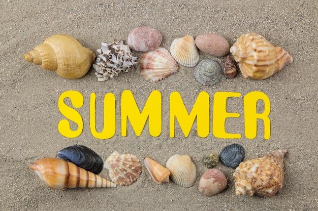Latem napis z papieru żółte litery i muszle na morskim piasku. lato. relaks. wakacje. widok z góry
