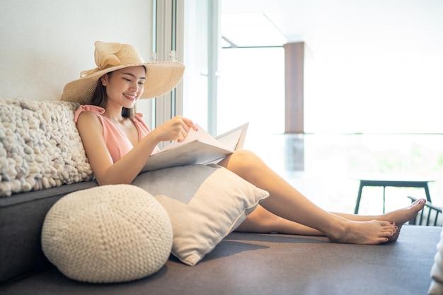 Latem piękna kobieta w różowym bikini siedzi i czyta książkę na wygodnym siedzeniu w pokoju.