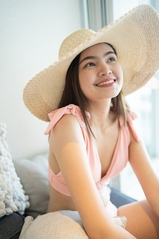 Latem piękna kobieta w różowym bikini usiądź na wygodnym siedzeniu w pokoju.