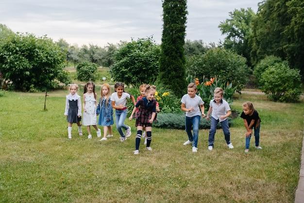 Latem po parku biegnie grupa dzieci w wieku szkolnym. szczęście, styl życia. szczęśliwe dzieciństwo.