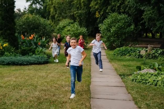 Latem po parku biegnie grupa dzieci w wieku szkolnym