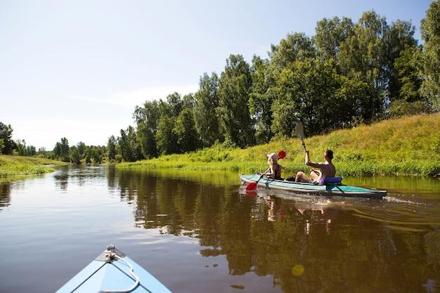 Latem po rzece pływa kajakiem para mężczyzn i kobiet. aktywny wypoczynek, rodzinne wakacje