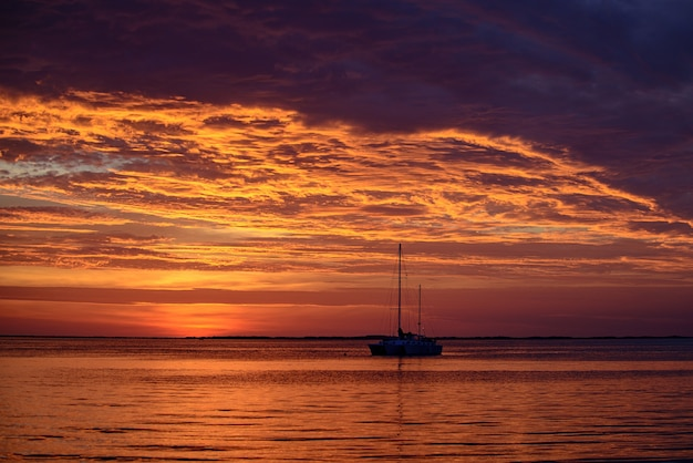 Latem podróżująca łódź jachtowa na wodzie o zachodzie słońca żaglówki na wodzie morskiej oceanu