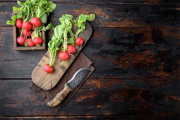 Latem zbierana czerwona rzodkiew. uprawa organicznych warzyw. duży pęczek surowego świeżego soczystego zestawu rzodkiewki ogrodowej, na starym ciemnym tle drewnianego stołu, widok z góry płaski, z kopią miejsca na tekst