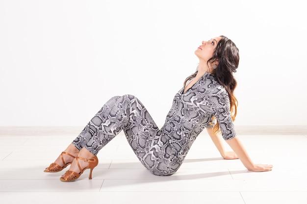Latin dance, bachata lady, jazz modern and vogue dance concept - piękna młoda kobieta tańczy na białej ścianie z miejsca na kopię
