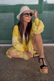 Latina dziewczyna w żółtej sukience i białym kapeluszu siedzi na ziemi na ulicy.