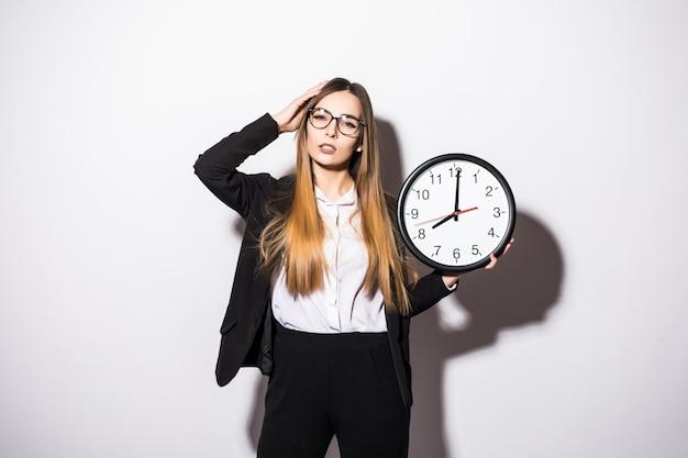 Lating młoda kobieta trzyma w rękach zegar na białym tle