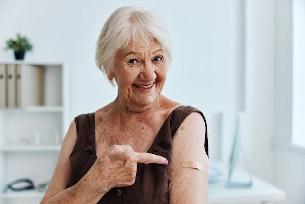 Łatka starej kobiety na ramieniu paszport szczepionkowy ochrona immunologiczna
