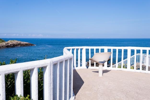 Lato biały plażowy krzesło z niebieskiego nieba tłem