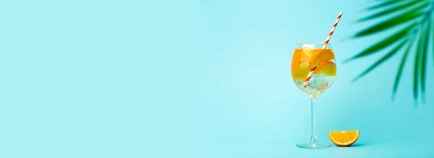Lato detox napój na niebieskim tle. lato zimny napój z pomarańczami i lodem na pustym kolorowym tle