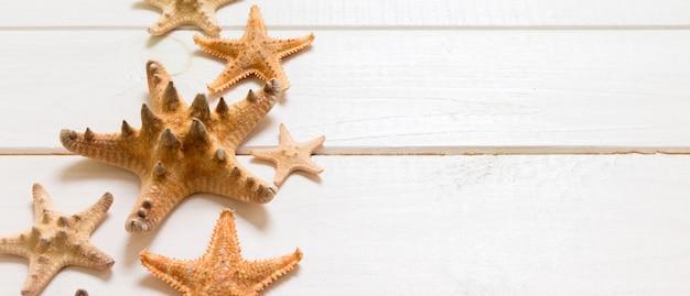 Lato drewniany stół z rozgwiazdą i seashells na białego tła odgórnym widoku. skopiuj miejsce transparent tło, koncepcja lato