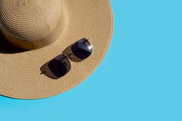 Lato kapelusz z okularami przeciwsłonecznymi na błękitnym tle. ciesz się wakacyjną koncepcją.
