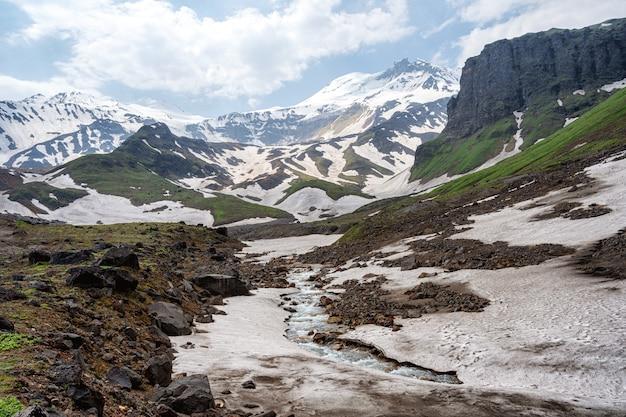 Lato krajobraz z rzecznym i halnym śniegiem.