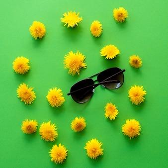 Lato lub wiosna tło żółte kwiaty mniszka lekarskiego i okulary przeciwsłoneczne na zielono