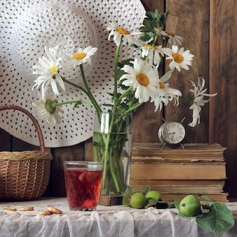 Lato martwa natura z bukietem stokrotek, kapelusz i kompot jagodowy w szkle.