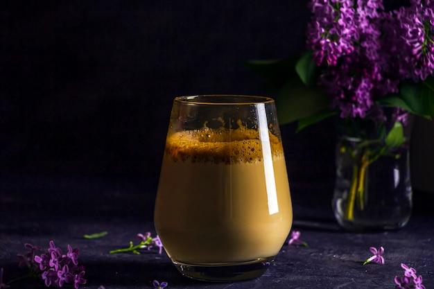 Lato martwa natura z kawą dalgona w wysokiej szklance i kwiatami bzu w ciemności. kawa rozpuszczalna bita z cukrem i wodą i dodawana do zimnego mleka. chłodny letni napój.