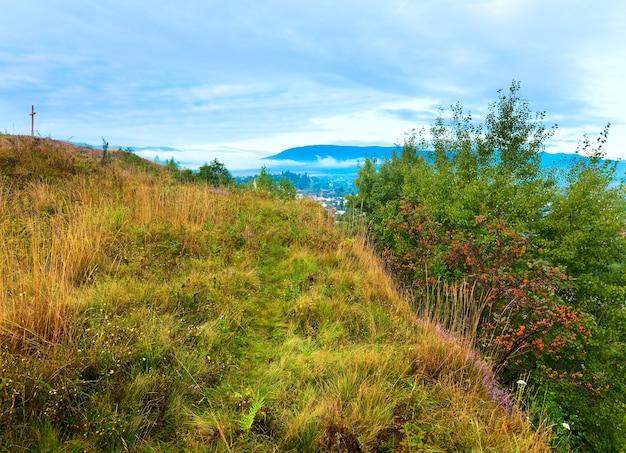 Lato mglisty poranek kraju podgórze widok z kwiatami wrzosu i drewniany krzyż (obwód lwowski, ukraina).