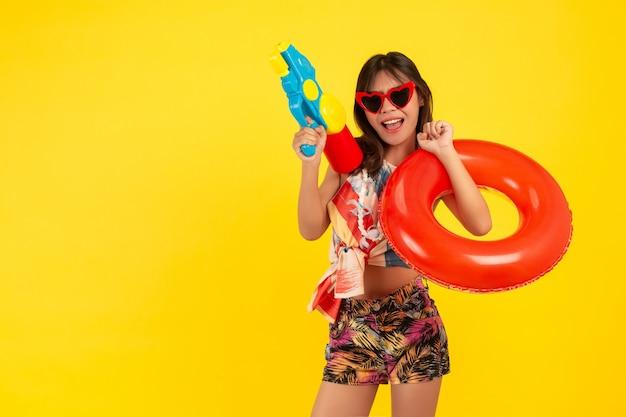 Lato młoda piękna kobieta z pistoletem na wodę i gumką, święta songkran