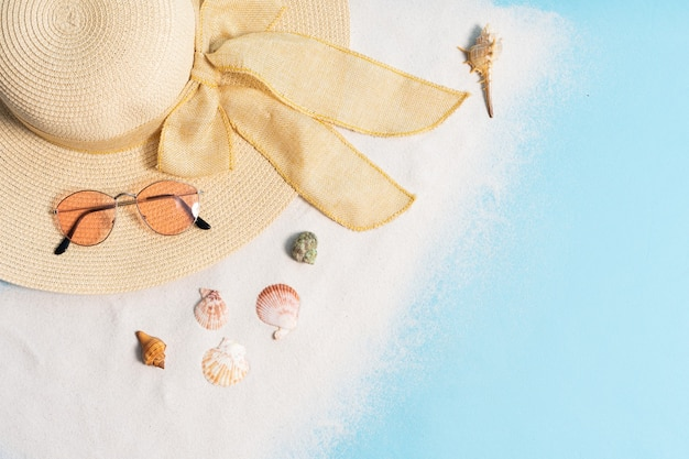 Lato na tle kapelusz, okulary przeciwsłoneczne, piasek i muszla