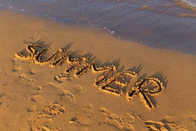 Lato napisane w piasku na plaży w pobliżu morza