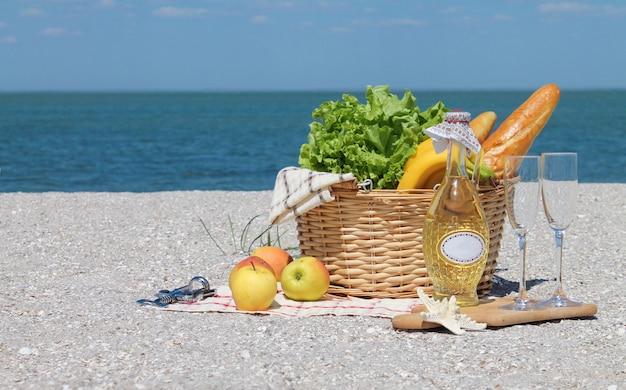Lato piknik tło z koszem, wino na plaży nad oceanem
