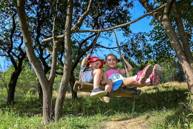 Lato po zamknięciu dwójki dzieci siedzących na huśtawce w górach z dala od zwykłego placu zabaw