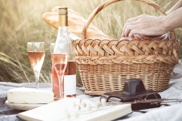 Lato - prowansalski piknik na łące. bagietka, wino, kieliszki, winogrona, ser brie, bagietka w koszu