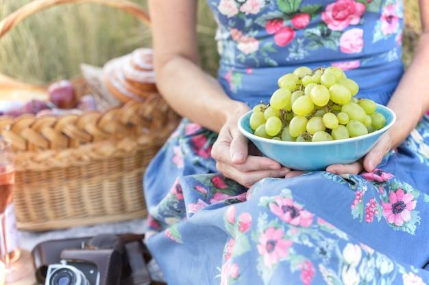 Lato - prowansalski piknik na łące. dziewczyna trzyma w rękach miskę winogron, a obok kosz piknikowy i bagietkę, wino, kieliszki, winogrona i bułki