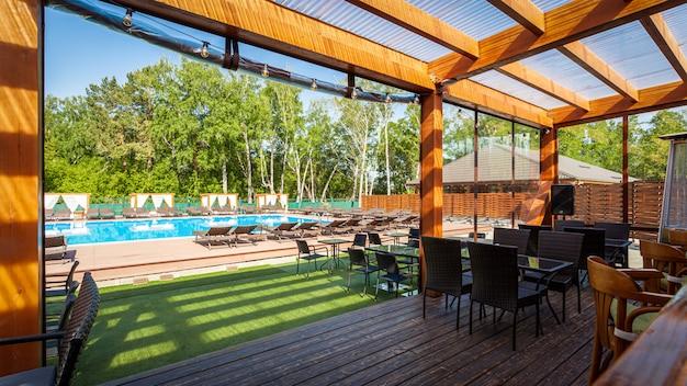 Lato pusta plenerowa kawiarnia przy parkiem. barowa kawiarnia o nowoczesnym designie, drewniane ściany, krzesła, stoły