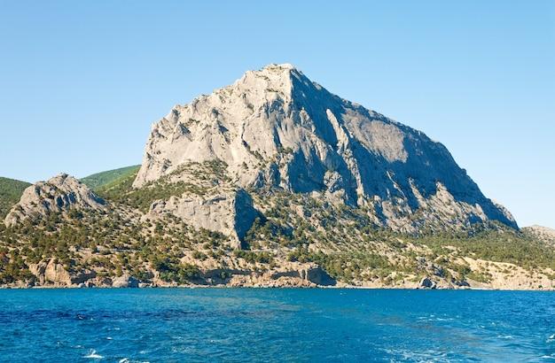 Lato skaliste wybrzeże na tle błękitnego nieba (skała