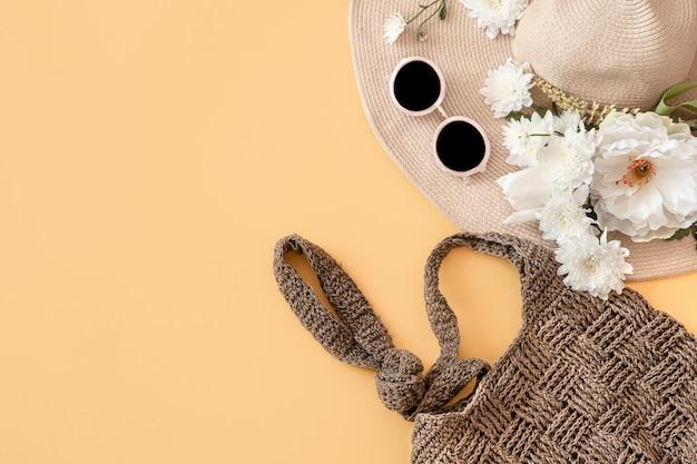 Lato stylowe z letnimi dodatkami, wiklinowa czapka, torba i okulary.