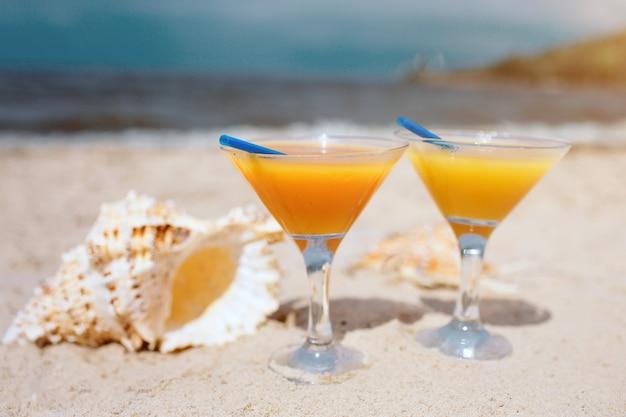 Lato: świeże egzotyczne pomarańczowe koktajle na plaży. poza tym piękna biała skorupa leżąca na piasku. słońce świeci jasno. poziomy widok pionowy. raj.