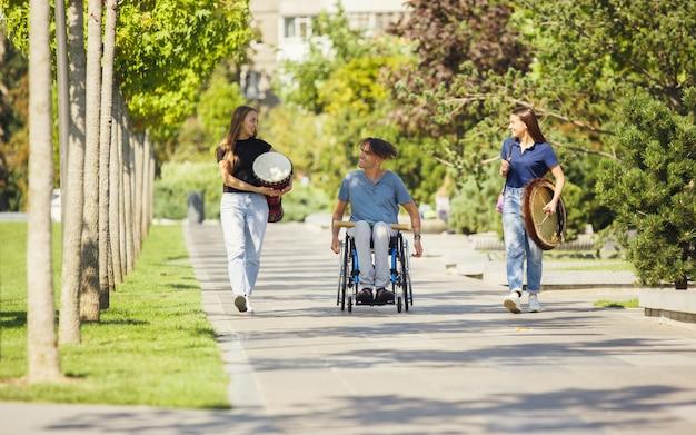 Lato. szczęśliwy kaukaski niepełnosprawny mężczyzna na wózku inwalidzkim, spędzając czas z przyjaciółmi grając muzykę instrumentalną na żywo na świeżym powietrzu. pojęcie życia społecznego, przyjaźni, możliwości, integracji, różnorodności.