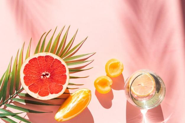 Lato tło wakacje płasko leżał liść palmowy owoce i liść palmy na różowym tle