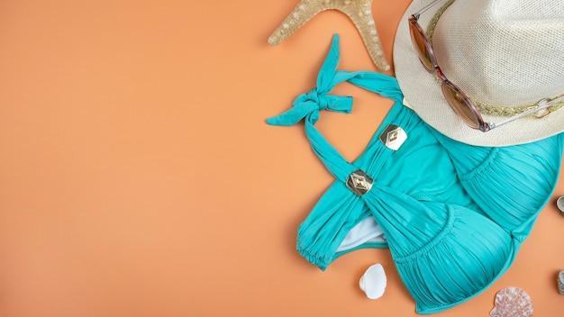 Lato tło z kapeluszem, okularami przeciwsłonecznymi, plażowym strojem kąpielowym i muszlami. widok z góry, kopia miejsca