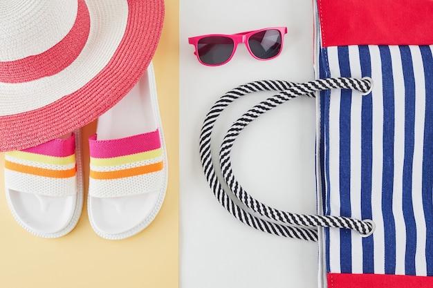 Lato tło ze słomkowym kapeluszem plażowym, okularami przeciwsłonecznymi, torbą i klapkami. koncepcja podróży letnich.