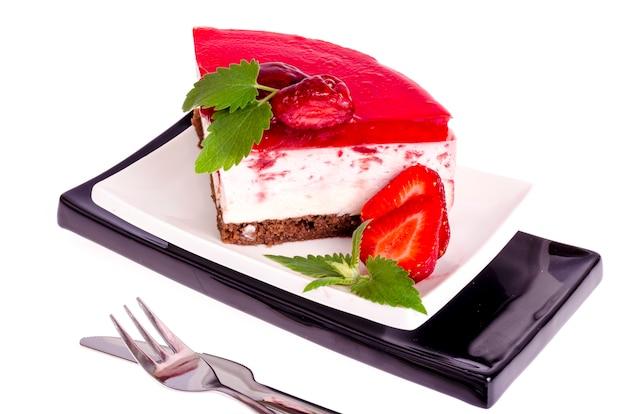 Lato truskawkowy mousse tort z świeżymi jagodami na białym tle.