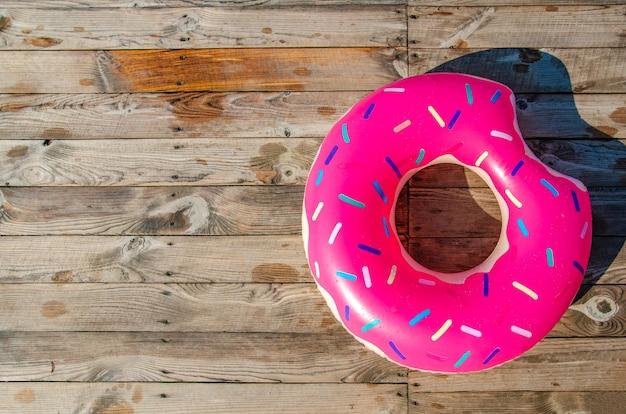Lato w tle. akcesoria plażowe, gumowy pierścień na drewnianym tarasie
