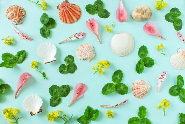 Lato w tle. muszle, zielone liście goździków i płatki na minimalnym niebieskim tle. miejsce na tekst copyspace
